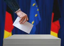 Election in Germany. Voter holds envelope in hand above vote ballot. German and European Union flags in background Stock Photos