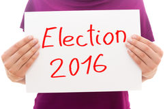 Election 2016. Girl holding white paper sheet with text Election 2016 Royalty Free Stock Image