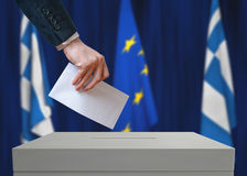 Election in Greece. Voter holds envelope in hand above vote ballot. Greek and European Union flags in background Royalty Free Stock Images