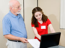 Election - Helpful Volunteer. Teen volunteer helping senior voter use the new equipment on election day Royalty Free Stock Photography