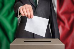 Election in Italy - voting at the ballot box. The hand of man putting his vote in the ballot box. Flag of Italy on background Stock Photos