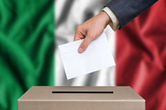 Election in Italy - voting at the ballot box. Election in Italy. The hand of man putting his vote in the ballot box. Italian flag on background Royalty Free Stock Photos