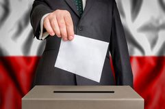 Election in Poland - voting at the ballot box. The hand of man putting his vote in the ballot box. Flag of Poland on background stock photo