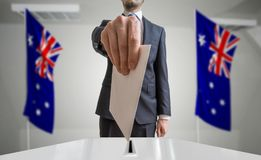 Election or referendum in Australia. Voter holds envelope in hand above ballot. Australian flags in background.  Stock Photos