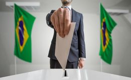 Election or referendum in Brazil. Voter holds envelope in hand above ballot. Brazilian flags in background.  Royalty Free Stock Image