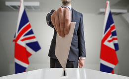 Election or referendum in Great Britain. Voter holds envelope in hand above ballot. United kingdom flags in background.  Stock Photography