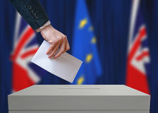 Election or referendum in Great Britain. Voter holds envelope in hand above vote ballot. British and European Union flags in background Stock Photo