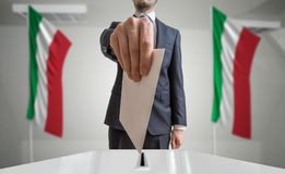 Election or referendum in Italy. Voter holds envelope in hand above ballot. Italian flags in background.  Stock Photo