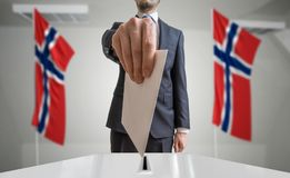 Election or referendum in Norway. Voter holds envelope in hand above ballot. Norwegian flags in background.  Stock Photos