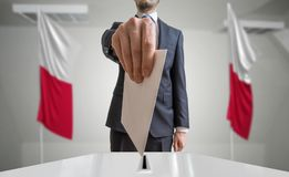 Election or referendum in Poland. Voter holds envelope in hand above ballot. Polish flags in background.  Stock Photo