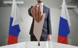 Election or referendum in Russia. Voter holds envelope in hand above ballot. Russian flags in background.  Royalty Free Stock Image