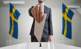 Election or referendum in Sweden. Voter holds envelope in hand above ballot. Swedian flags in background.  Royalty Free Stock Image