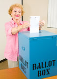 Election - Senior Woman Casts Ballot. Senior woman at the polls casting her ballot in the box Royalty Free Stock Photography