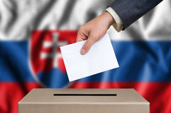 Election in Slovakia - voting at the ballot box. Election in Slovakia. The hand of man putting his vote in the ballot box. Slovak flag on background royalty free stock image