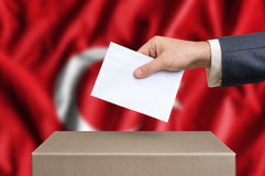 Election in Turkey - voting at the ballot box. Election in Turkey. The hand of man putting his vote in the ballot box. Turkish flag on background stock photos