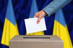 Election in Ukraine - voting at the ballot box. Election in Ukraine. The hand of woman putting her vote in the ballot box. Ukrainian flags on background Stock Photography