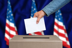 Election in United States of America - voting at the ballot box. Presidential election in United States of America. The hand of woman putting her vote in the Stock Image