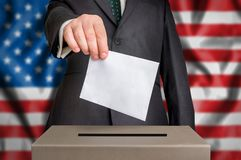 Election in USA - voting at the ballot box. Election in United States of America - voting at the ballot box. The hand of man putting his vote in the ballot box Stock Image