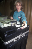 Election volunteer depositing ballots. In a ballot box in a polling place, CA Stock Photography