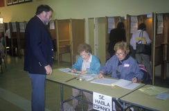 Election volunteers assisting voters in a polling place, CA Stock Images