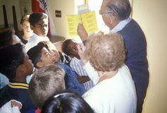 Election volunteers instructing young people on voting procedures in a polling place, CA Stock Photo