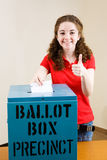 Election - Young Voter Thumbsup. Young first time voter casting her ballot and giving a thumbs-up sign Stock Image