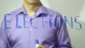 Elections inscription businessman writes on glass video 4k. Elections inscription businessman writes video 4k stock video footage