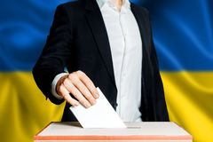 Elections in Ukraine, political struggle. Democracy, freedom and independence concept. Citizen Voter Putting Ballot In to Voting b. Elections in Ukraine stock photography