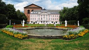 Electoral Palace. Merzig,Germany - 1 August,2010: People walking and taking photos at pink,baroc electional palace behind fountain in summer in Germany at sunny Royalty Free Stock Photos