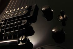 Electric. A close-up image of a black electric guitar, showing the details of the strings, buttons, and knobs Royalty Free Stock Photography