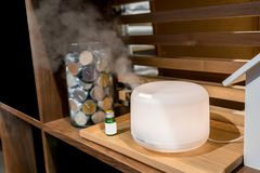 Electric aroma oil diffuser on wooden floor. With green glass bottle stock image