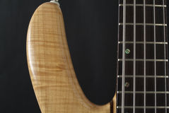 Electric bass guitar. Part of electric bass guitar, over black Stock Photography