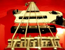 Electric Bass Guitar. Red electric bass guitar detail over red background stock photography