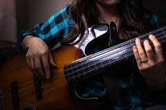An electric bass guitar being strum. A fretless electric bass guitar being played by a young woman in the natural light. Up-close on a hands strumming the stock image