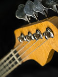 Electric bass guitar closeup. Photo of a bass guitar headstock over black background Royalty Free Stock Photos
