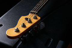 Electric Bass guitar headstock on black leather hard case Stock Image