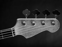 Electric bass guitar headstock. Black and white photo of a bass guitar headstock over dark background Royalty Free Stock Photos