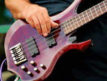 Electric bass guitar. Man playing his electric bass guitar in concert outdoors stock photos