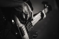Electric bass guitar player hands, live music. Theme, close up black and white photo royalty free stock photo