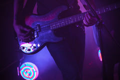 Electric bass guitar player in purple light. Live rock music background, electric bass guitar player in purple stage lights, closeup photo with soft selective Royalty Free Stock Photography
