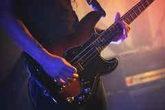 Electric bass guitar player, close up photo. Electric bass guitar player on a stage, closeup photo with soft selective focus Stock Photo