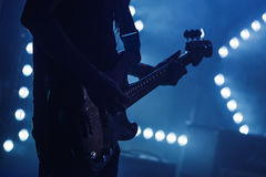 Electric bass guitar player on stage. Live rock music background, electric bass guitar player in blue lights, closeup silhouette photo with soft selective focus Royalty Free Stock Image