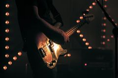 Electric bass guitar player on a stage. Electric bass guitar player on the stage with strobe illumination background, live hard rock music theme Stock Photos