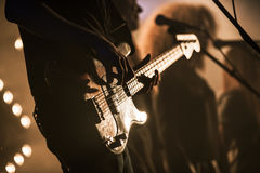 Electric bass guitar player on the stage. With strobe illumination, live hard rock music theme Stock Images