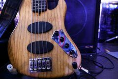 Electric bass guitar stands on the stage. Close up stock photography
