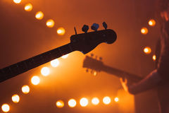 Electric bass and solo guitar silhouettes. Live music background, electric bass and solo guitar silhouettes, close-up photo with soft selective focus royalty free stock images