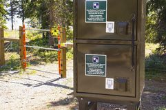 Electric bear fence and bear-resistant food lockers. Electric bear fence around tenting area  and bear-resistant food storage lockers at a Yukon campsite, Canada stock image