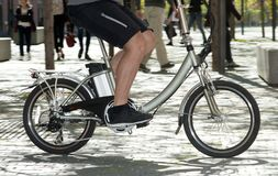 Electric bicycle through the city. Electric bicycle runs through the city among pedestrians royalty free stock photography