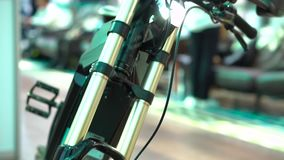 Electric bicycle details closeup, front wheel, shock absorbers on steering tube. With unfocused people behind stock video