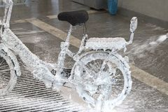Electric bicycle in foam in a car wash. Washing a bike with a jet of foam royalty free stock images